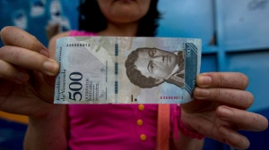 A bank customer shows a new bank note of 500 Bolivars outside a bank in Caracas, Venezuela, Monday, Jan. 16, 2017. (AP Photo/Fernando Llano)