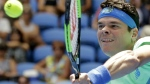 Canada's Milos Raonic makes a backhand return to Germany's Dustin Brown during their first round match at the Australian Open tennis championships in Melbourne, Australia, Tuesday, Jan. 17, 2017. (AP / Aaron Favila)