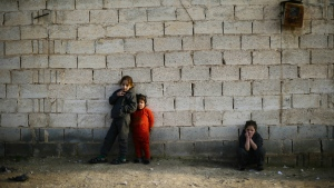 Syrian girls who fled from the village of Deir Hafer with their family watch their brothers playing in the town of Safira, just south of Aleppo, Syria on Wednesday, Jan. 18, 2017. (AP / Hassan Ammar)