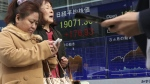 People use mobile phones in front of an electronic stock indicator of a securities firm showing Japan's benchmark Nikkei 225 in Tokyo on Thursday, Jan. 19, 2017. (AP / Shizuo Kambayashi)