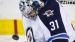 Winnipeg Jets goalie Ondrej Pavelec, of the Czech Republic, blocks a shot during second period NHL hockey action against the Calgary Flames in Calgary, Wednesday, March 16, 2016. THE CANADIAN PRESS/Jeff McIntosh