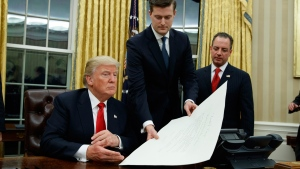 White House Chief of Staff Reince Priebus, right, watches as White House Staff Secretary Rob Porter, centre, hands U.S. President Donald Trump a confirmation order in the Oval Office of the White House, on Jan. 20, 2017. (Evan Vucci / AP)