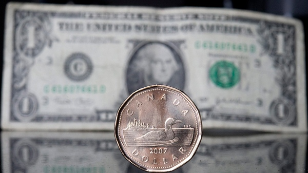 A Canadian dollar, or loonie, sits in front of the American dollar in Ottawa, Thursday Sept. 20, 2007. (Jonathan Hayward / THE CANADIAN PRESS)