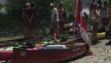 Participants gather around docked boats after a flotilla to honour adventurer Don Starkell.