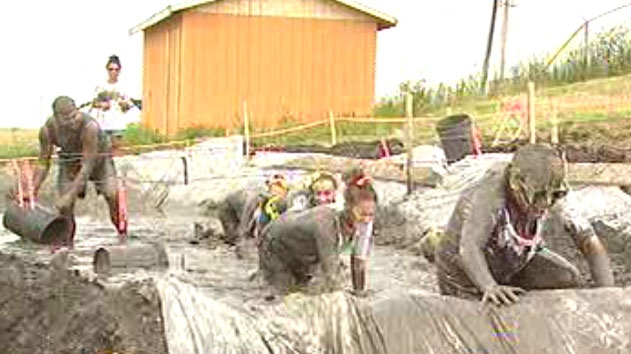 Participants get soaked with mud before the finish line at the Dirty Donkey Mud Run on Saturday.