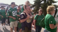 Blue Bombers and Roughriders fans line up outside Mosaic Stadium in Regina Saturday.