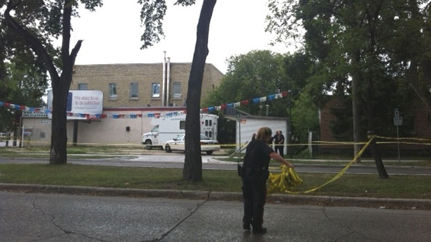 Winnipeg police move police tape at Burrows Avenue and Main Street where they investigated Sunday.